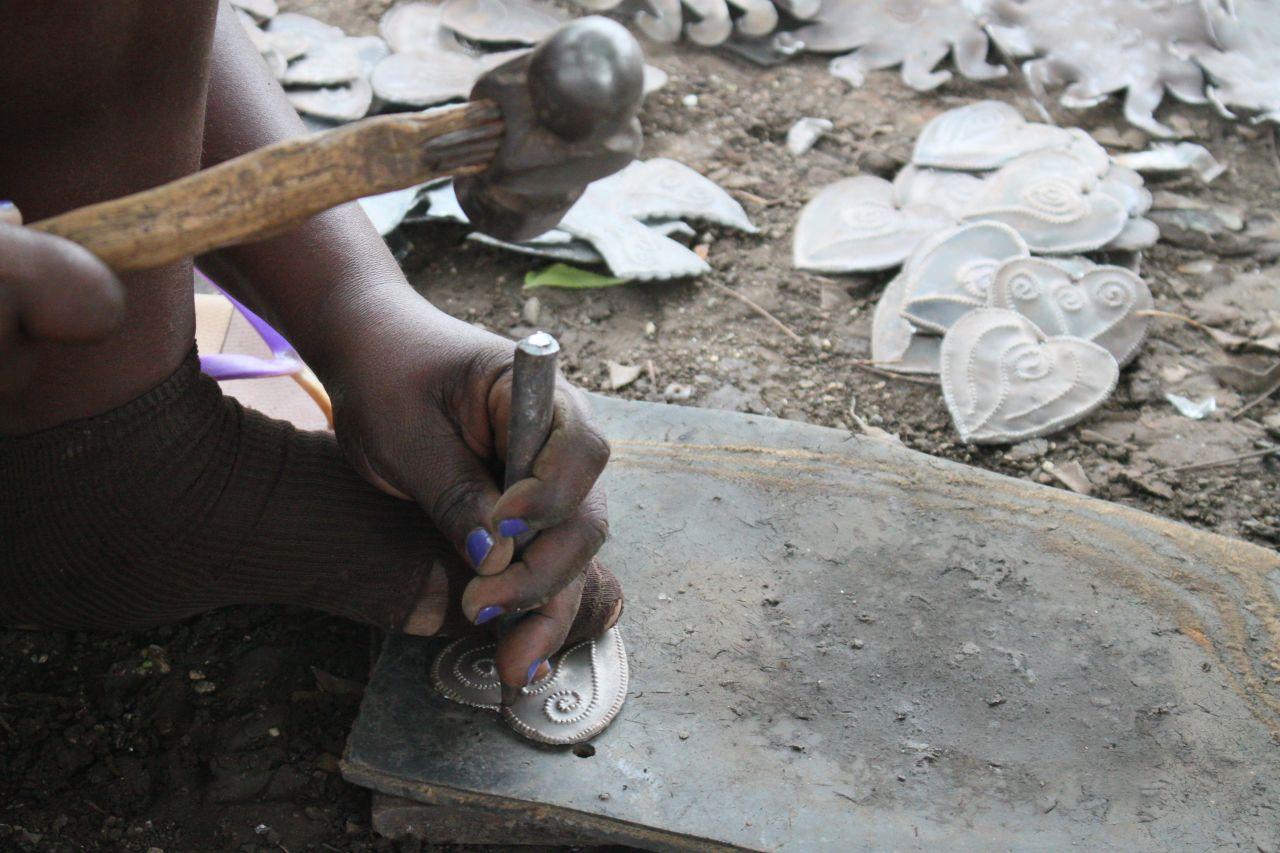 De metaalkunstenaars werken zittend op de grond, zonder enige bescherming