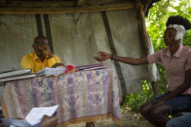 Een vrouw betaalt 25 HTG voor een plastic beschermhoes